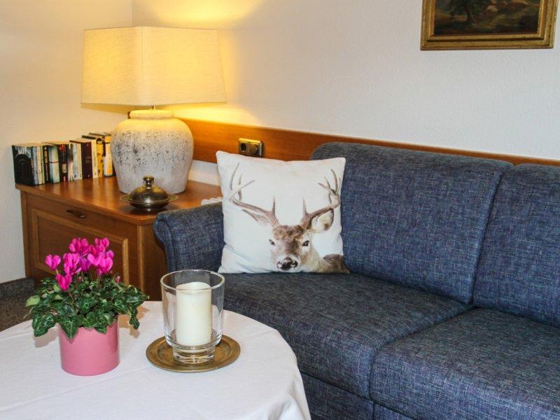Alpennest Wohnraum mit gemütlichem Sofa zum Ausziehen