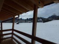 Blick vom Balkon in die verschneite Winterlandschaft
