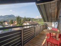 Sonniger Balkon mit Esstisch und Liegestühlen